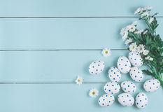 Easter eggs and white flowers on wooden background. White of egg with a pattern of blue circles Stock Image