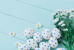 Easter eggs and white flowers on wooden background. White of egg with a pattern of blue circles Royalty Free Stock Photos