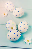 Easter eggs and white flowers on wooden background. White of egg with a pattern of blue circles Royalty Free Stock Image