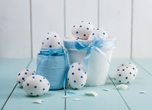 Easter eggs and white flowers on wooden background. Easter eggs in pot on wooden background. White of egg with a pattern of blue circles Stock Photo