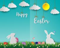 Easter eggs with white rabbits on green grass,cute paper art on soft blue background for happy holiday stock photos