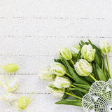 Easter eggs and white tulips on vintage tablecloth. Top view, copy space, Easter background. Royalty Free Stock Photo