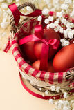 Easter eggs in the whitish nest and white flowers. On the beige table Stock Photography
