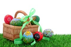 Easter eggs in wicker basket. Hand painted beautiful  colorful  easter eggs in wicker basket on fresh green grass Royalty Free Stock Photos