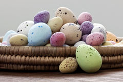 Easter eggs in a wicker basket. Still life photo of speckled candy covered chocolate easter eggs in a wicker basket on a rustic wooden table Royalty Free Stock Photography