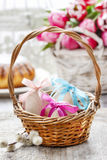 Easter eggs in wicker basket Stock Photos