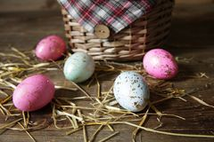 Easter eggs on a wicker basket background on a wooden rustic table stock photo