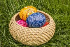 Easter Eggs in Wicker Basket. In grass stock photos