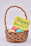 Easter Eggs in wicker basket. Happy Easter greeting card Stock Image