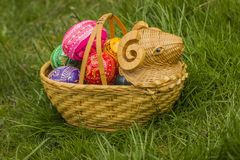 Easter Eggs in Wicker Basket in the shape of lamp. On grass stock image