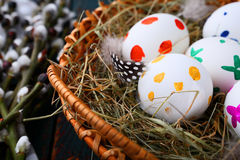 Easter eggs in a wicker basket on straw Stock Photography