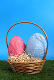 Easter eggs and wicker basket on a studio garden Stock Photos