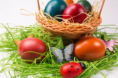Easter eggs in wicker basket on white Stock Photography
