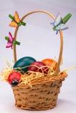 Easter eggs in wicker basket on white Stock Photos