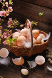Easter eggs in wicker basket on wooden background Royalty Free Stock Images
