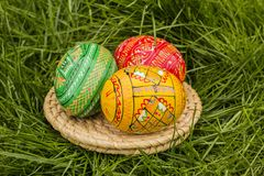 Easter Eggs on Wicker Plate. In grass stock images