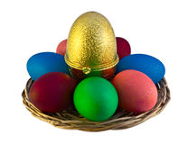 Easter eggs in wicker plate over white. Easter eggs with big golden egg-like box in wicker plate against a white background Royalty Free Stock Photo