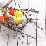 Easter eggs and willow branches in basket Stock Photos