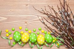 Easter eggs and willow branches on wooden background. Royalty Free Stock Photo