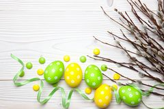 Easter eggs and willow branches on wooden background. Stock Photo