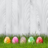 Easter eggs on a wood background. Decorative Easter eggs in grass on a wood background Royalty Free Stock Image