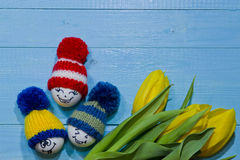 Easter eggs on wood. Emoticons in knitted hat with pom-poms. A b Royalty Free Stock Images