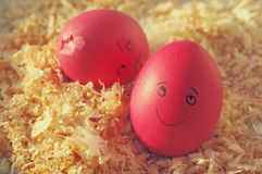 Easter eggs on wood sawdust. Two amusing Easter eggs with the drawn persons. Stock Image