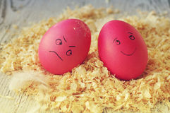 Easter eggs on wood sawdust. Two amusing Easter eggs with the drawn persons. Royalty Free Stock Image