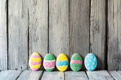Easter eggs on a wooden background, iced biscuits stock photos