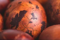 Easter eggs on wooden background. Painted brown with spots and cracks. Selective focus macro shot with shallow DOF.  royalty free stock images
