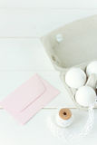 Easter eggs on wooden background with pink envelope stock photography
