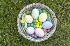 Easter eggs in wooden basket on grass royalty free stock photos