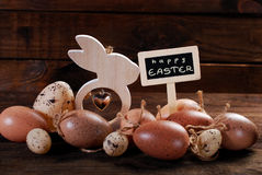 Easter eggs and wooden decorations with greetings on chalkboard Stock Photos