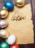 Easter eggs on wooden table with blank paper for text. Royalty Free Stock Photos