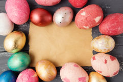 Easter eggs on wooden table with blank paper for text. Royalty Free Stock Image