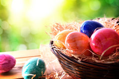 Easter eggs on a wooden table in nature elevated view. Easter eggs on a wooden table and a basket in the field. Horizontal composition. Elevated view royalty free stock photos