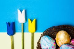 Easter eggs with wooden tulips decoration. On pastel background Stock Photo