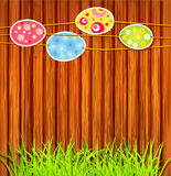 Easter eggs on a wooden wall. The Easter eggs on a wooden wall background with grass Stock Image