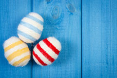 Easter eggs wrapped woolen string on blue wooden boards, copy space for text, decoration for Easter Stock Photography