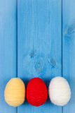Easter eggs wrapped woolen string on blue wooden boards, copy space for text, decoration for Easter Stock Image