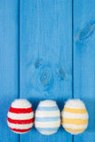 Easter eggs wrapped woolen string on blue wooden boards, copy space for text, decoration for Easter Royalty Free Stock Image