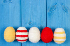 Easter eggs wrapped woolen string on blue wooden boards, copy space for text, decoration for Easter Stock Photos