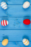 Easter eggs wrapped woolen string on blue wooden boards, copy space for text, decoration for Easter Royalty Free Stock Images
