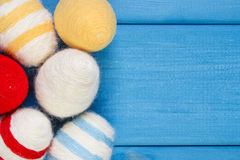 Easter eggs wrapped woolen string on blue wooden boards, copy space for text, decoration for Easter Royalty Free Stock Photos