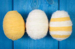 Easter eggs wrapped woolen string on blue wooden boards, decoration for Easter Royalty Free Stock Photography