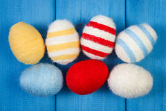 Easter eggs wrapped woolen string on blue wooden boards, decoration for Easter Royalty Free Stock Photos