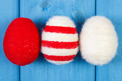 Easter eggs wrapped woolen string on blue wooden boards, decoration for Easter Royalty Free Stock Images