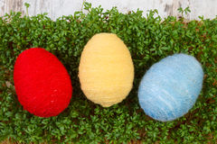 Easter eggs wrapped woolen string and green cress, decoration for Easter Royalty Free Stock Photo