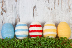 Easter eggs wrapped woolen string and green cress on wooden background, copy space for text, decoration for Easter Royalty Free Stock Photography