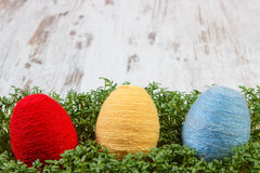 Easter eggs wrapped woolen string and green cress on wooden background, copy space for text, decoration for Easter Royalty Free Stock Image